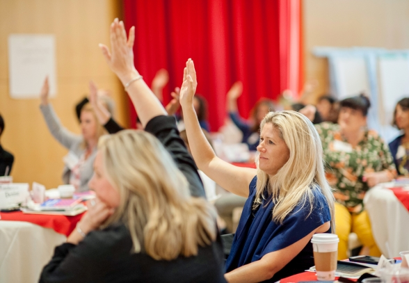Women raising their hands in a session